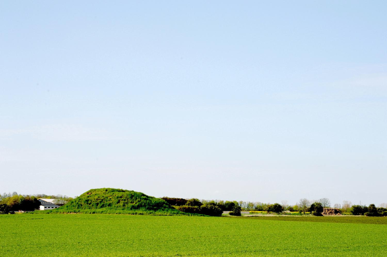 Rundhøj på grøn mark. Bag højen anes nyere landbrugsbygning