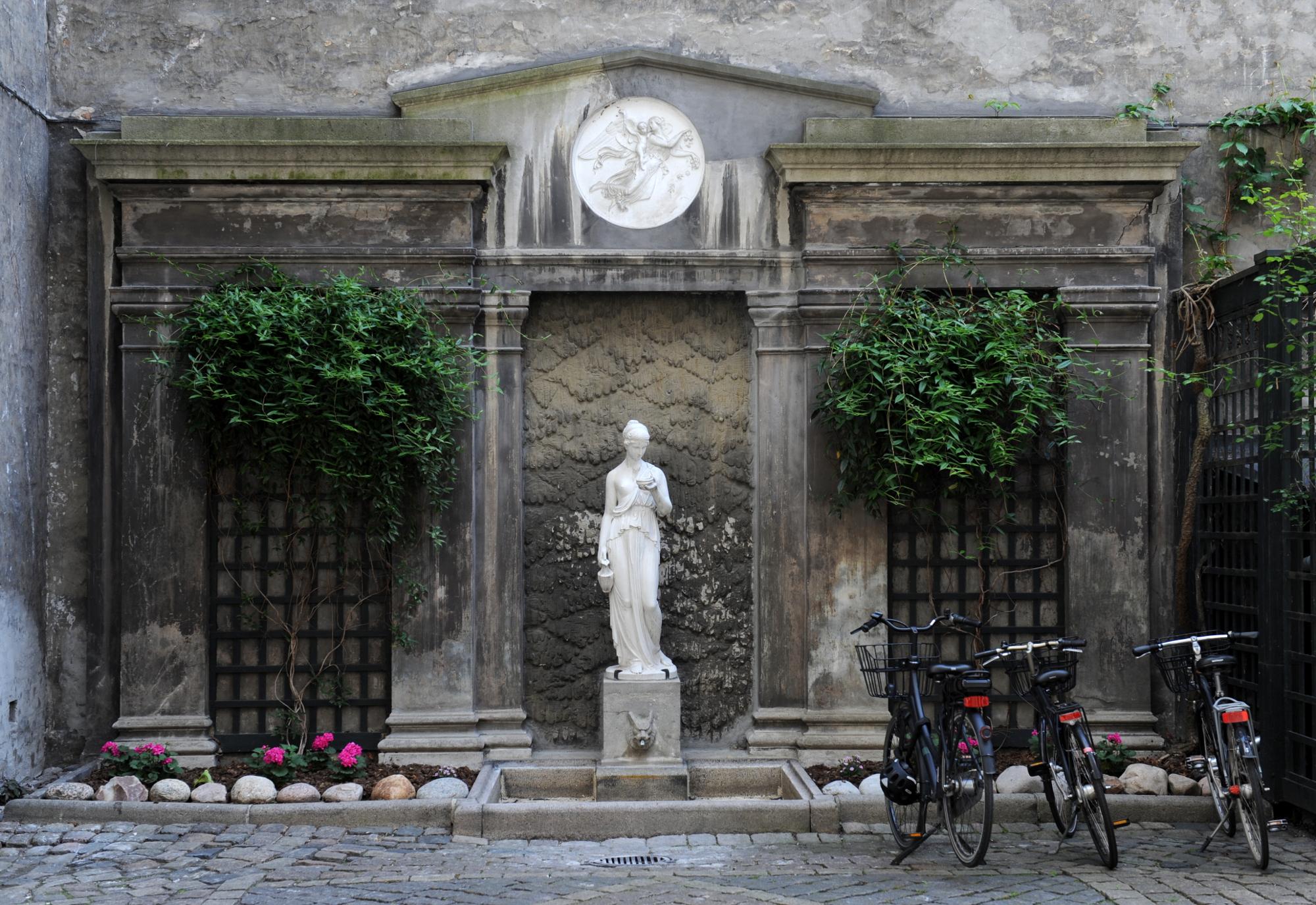 Skulptur af marmor foran facade formet som forsiden af et antik tempel