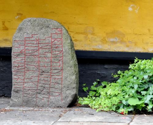 Runesten foran gul væg