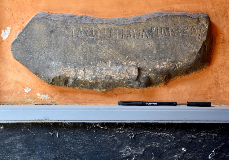 Runesten indmuret i gulkalket væg