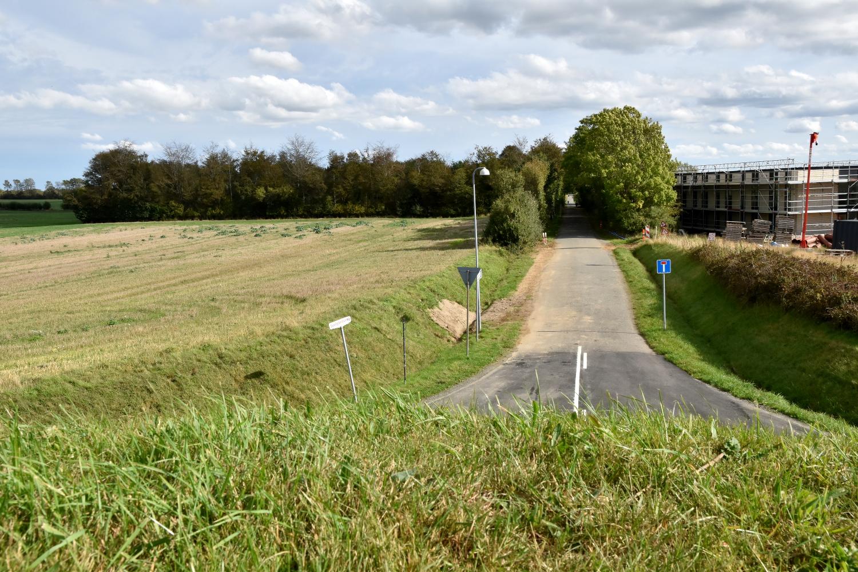 Udsigt fra gravhøj. I den ene side ses en boligblok og en blind vej. På den anden side ses en høstet mark.