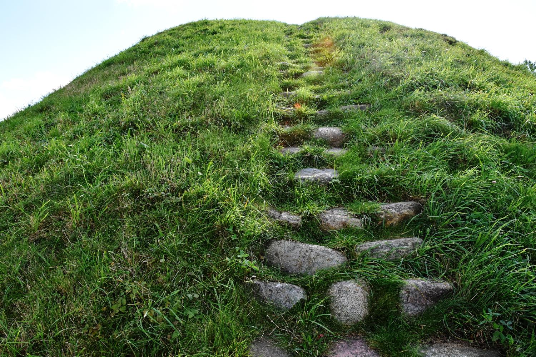 Ujævn trappe bygget af marksten. Trappen fører op at gravhøjens side.