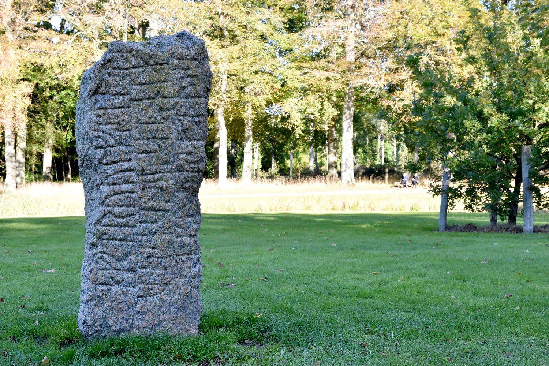 Runesten på græsplæne i park.