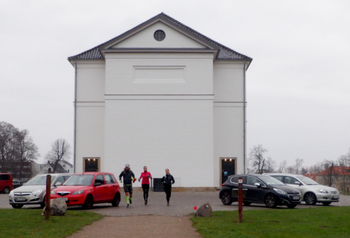 Bagsiden af kirken. Tre løbere og fire parkerede biler.
