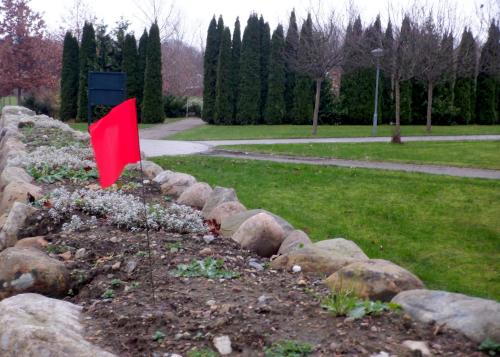 Rødt flag på kirkegårdsmur.