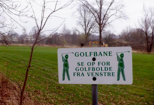 "Skilt med teksten ""Se op for golfbolde fra venstre""."