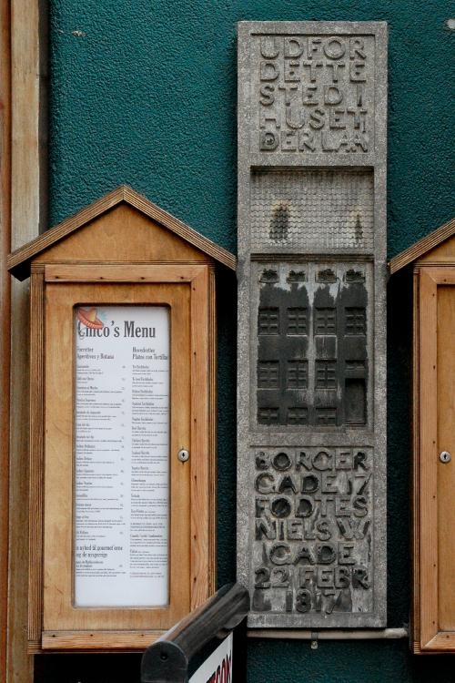 Mindetavle med tekst og reliefbillede af husfacade.