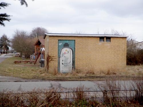 Gult murstensskur med graffiti.
