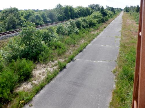 Lang asfaltvej langs jernbane.