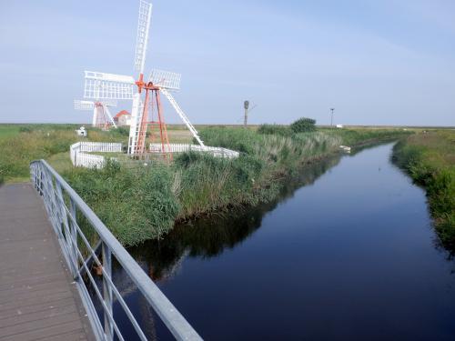 Pumpemøller i landskab med kanal