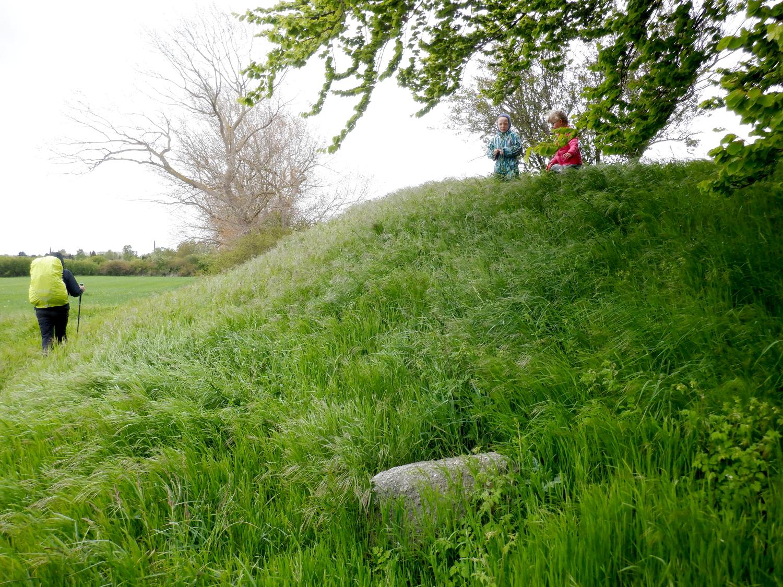 Siden af en gravhøj. På toppen af højen står et par børn og en vandre går væk langs højens fod