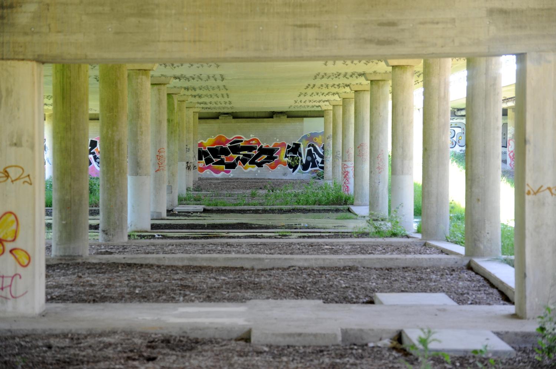 Betonkonstruktion med søjler. På betonvæg ses graffiti