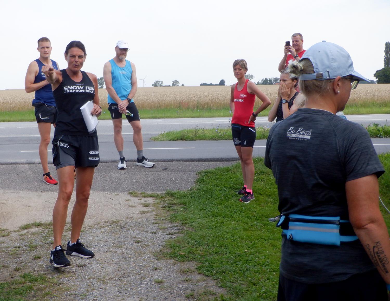 Kvinde omgivet af andre løber der lytter til hendes forklaring