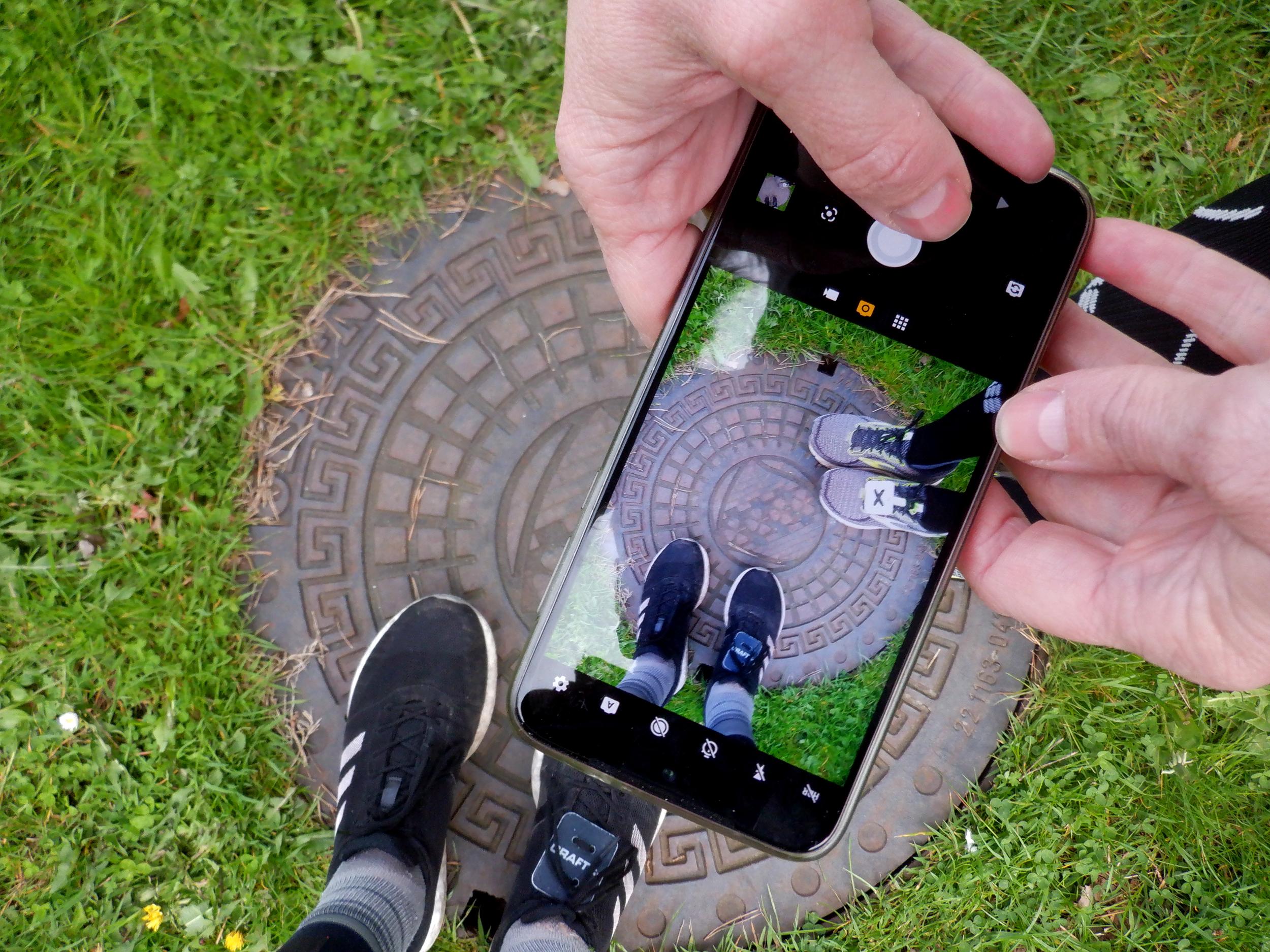 Mobil der tager fotos af sko og brønddæksen
