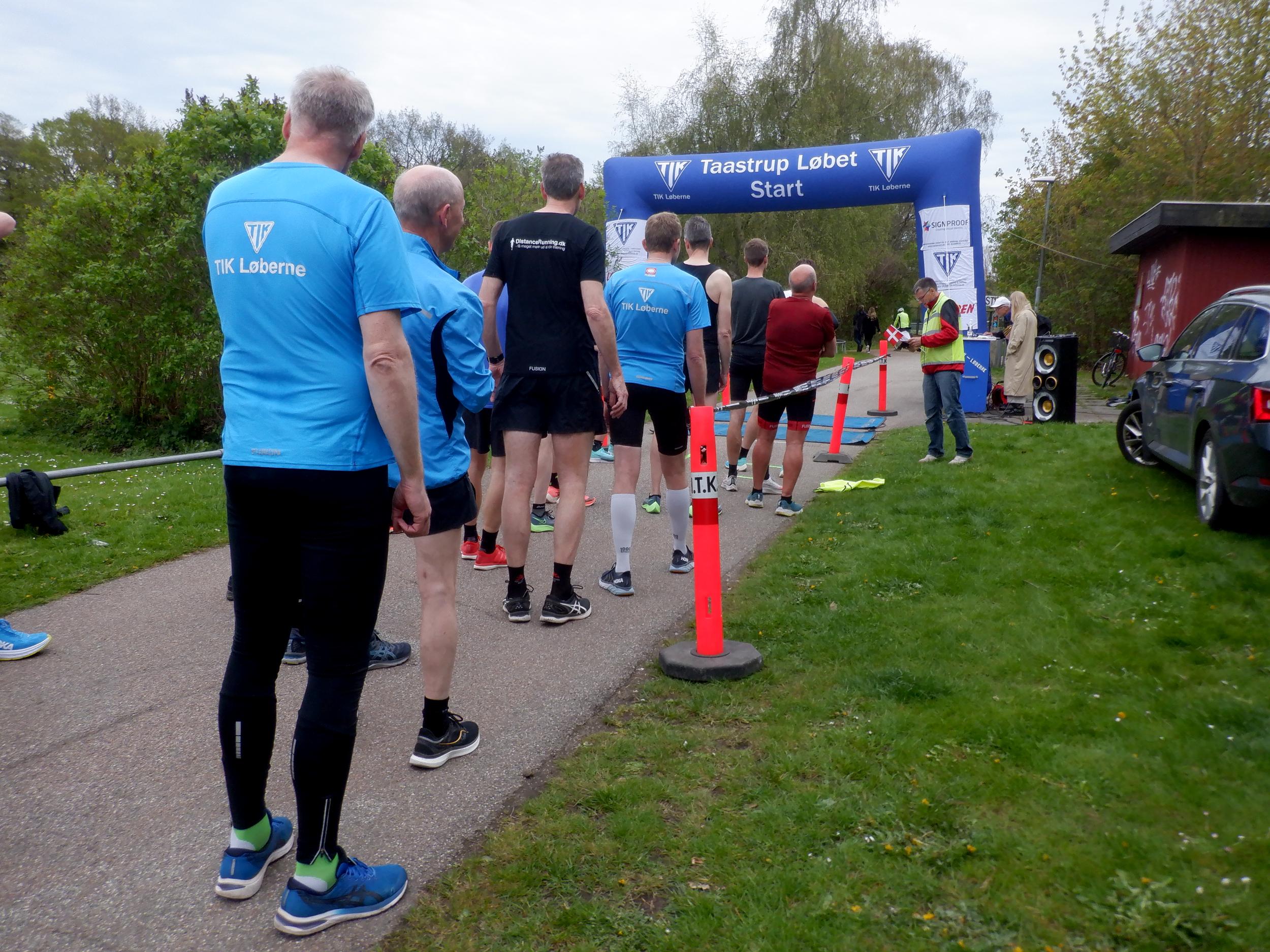 Løbere står i række bag start- og målportal