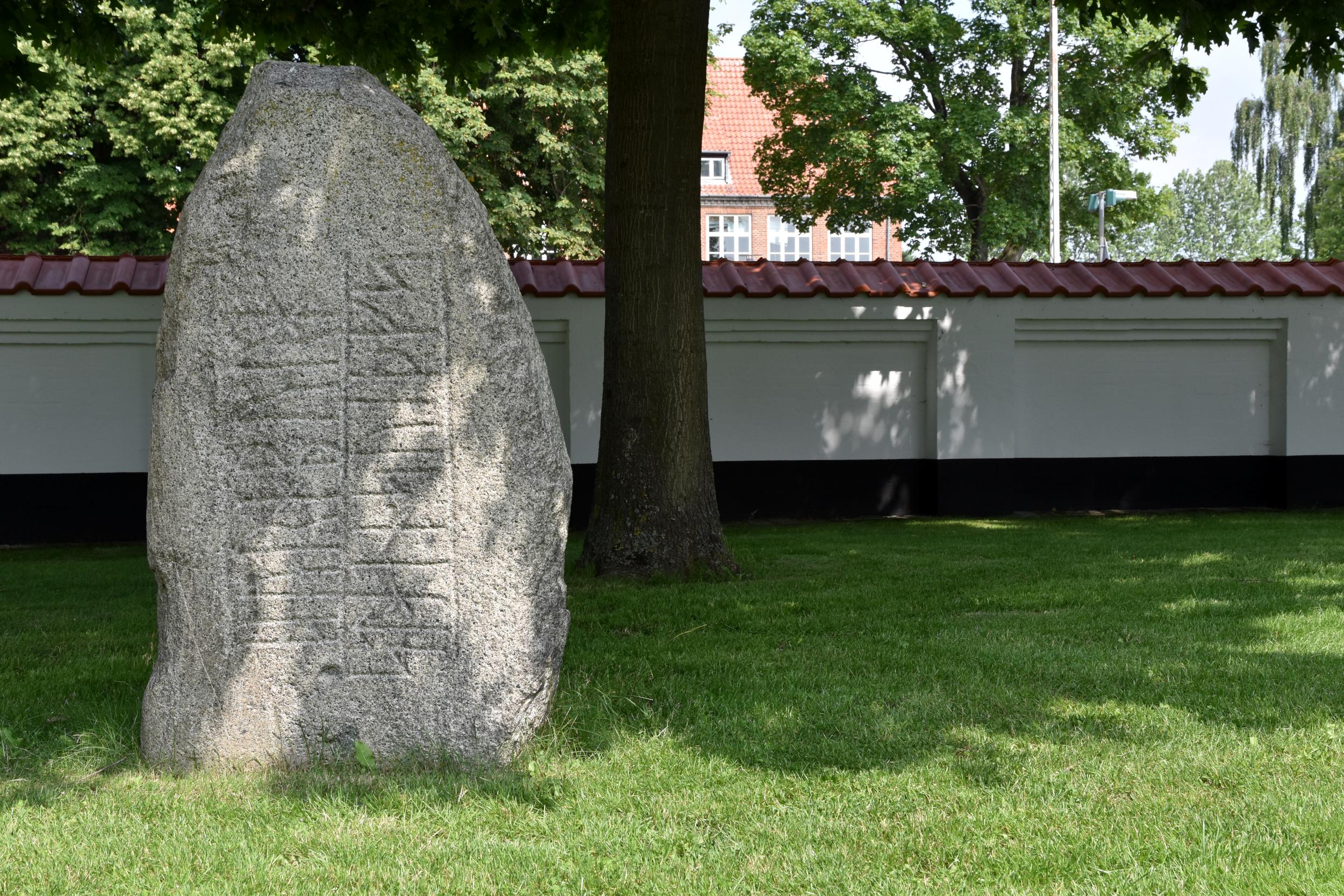 Runesten på grænplæne foran mur